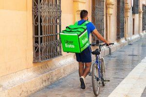 Uber Eatsの鞄を背負って自転車を押す人