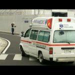 工事現場の誘導員が救急車を誘導する