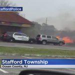 レストラン前で炎上する車を押し出すパトカー