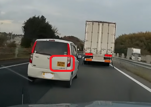 速度制限厳守中というステッカーが貼られた軽自動車