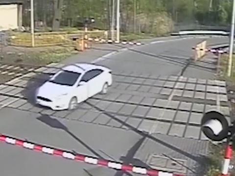 向かってくる電車と白い車