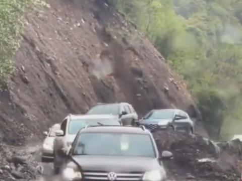 崖が崩れてくる中を通過する車たち