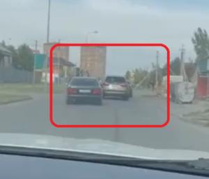 前の車を追いかける黒いセダン
